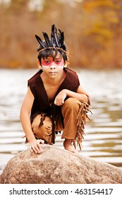 Young Native American.  Adorable young boy dressed as a Native American squatting on a rock.