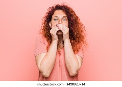 Young natural and authentic redhead woman shocked covering mouth with hands.