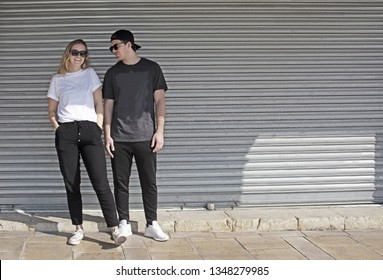 Young natural and casual sporty couple dressed man with cap backwards and woman against corrugated iron wall street style