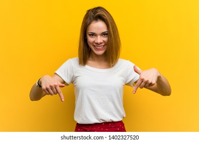 Young natural caucasian woman points down with fingers, positive feeling.