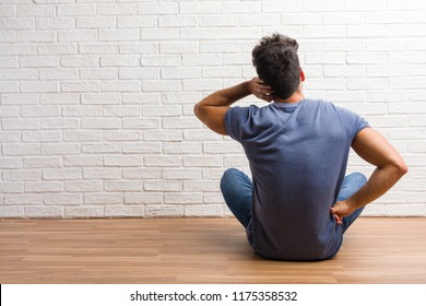 Young natural man sit on a wooden floor showing back, posing and waiting, looking back