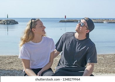 Young natural smiling and casual sporty couple sit on stone wall in sunshine by the ocean in Mallorca, Spain.