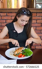Young natural woman enjoys her dinner