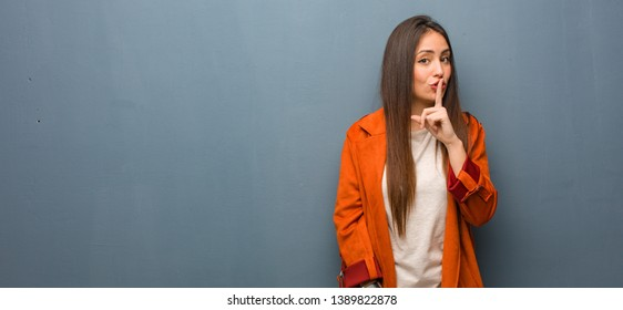 Young natural woman keeping a secret or asking for silence