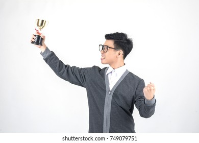 Young nerd man holding a trophy and smiling while standing against white background
