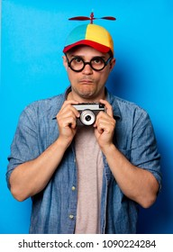 Young nerd man with noob hat holding a vintage photo camera on blue background