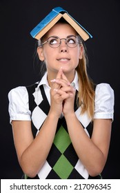 Young nerd woman crazy expression in glasses, holding book on head on black background