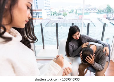 Young nervous couple talking with psychologist. Psychologist taking notes and explaining something to them
