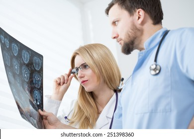 Young neurologists reading brain MRI at hospital
