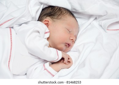 A young newborn baby is sleeping on a white bed with a blanket.