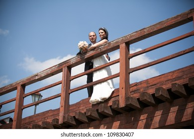Young newly married couple standing on the bridge