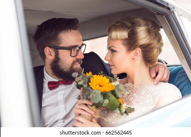 Young newlywed couple sitting in a retro vintage car, hugging and going away on a honeymoon. Focus on the bride