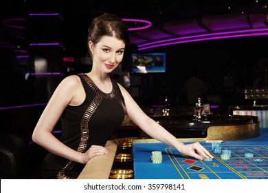 Young nice brunette lady with roulette table in casino
