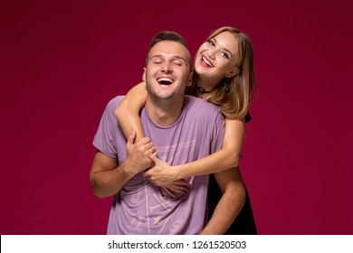 Young nice couple posing in the studio, express emotions and gestures, smiling, on a burgundy background