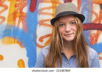 Young nice fashionable girl in a straw hat near the mural wall.