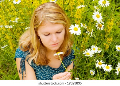 Young nice girl with close eyes lying in grass and relaxing with chamomile