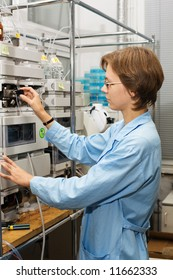 The young nice woman-scientist work with scientific instrument on a background scientific instruments