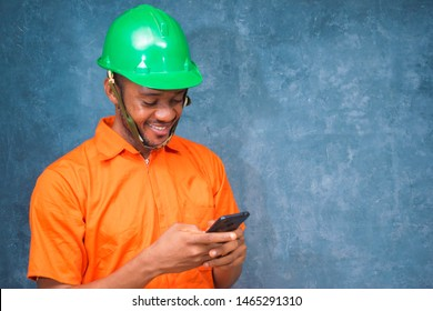 a young Nigerian engineer feels happy as he is browsing through his phone