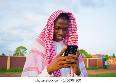a young Nigerian man feels happy by what he saw on his phone
