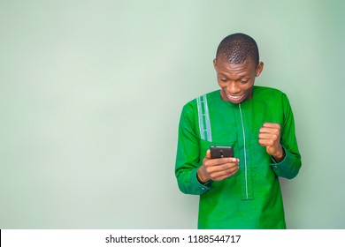 young nigerian man wearing green attire excited and happy about something he's looking at on his mobile phone.