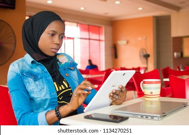 young nigerian muslim girl sitting alone in a fast food restaurant using her android tablet