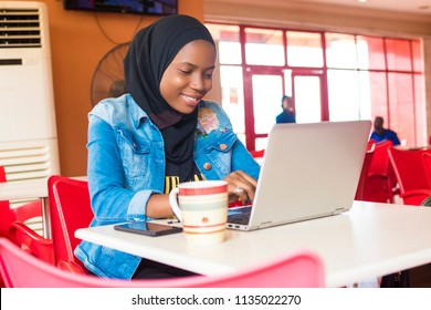 young nigerian muslim woman sitting alone in a cafe smiling while using her laptop