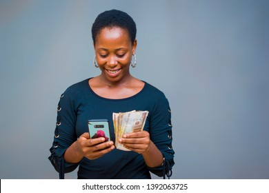 a young Nigerian woman happily operating her phone with her money on the other hand