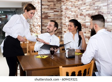 Young nippy serving table with happy adults in restaurant