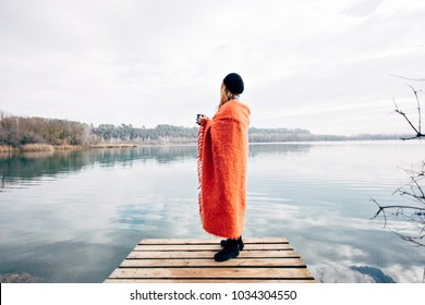 Young nomad adventurer and traveller during camping travel trip stands on edge of pier or boardwalk, snuggled in throw blanket or plaid, drinks coffee on morning, looks at lake, inspired and dreamy