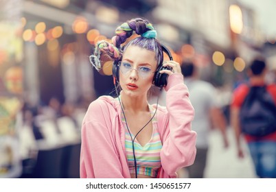 Young nonconformist girl listening music in headphones on the crowded streets. Blurred urban background. Vanguard fashion. Avantgarde hipster crazy style