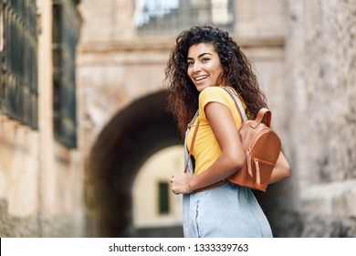 Young North African tourist woman with black curly hairstyle outdoors. Arab traveler girl in casual clothes in the street. Happy female with backpack.