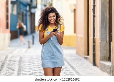 Young North African woman walking on the street looking at her smart phone. Smiling Arab girl in casual clothes with black curly hairstyle.