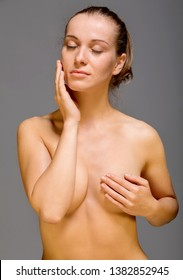 Young nude woman with covered breast touching face. Skin pampering concept.