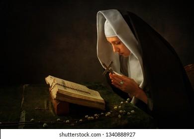 young nun praying in dark room