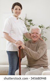 Young nurse caring for old man with walking stick