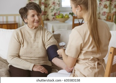 Young nurse checking senior woman's blood pressure in a living room