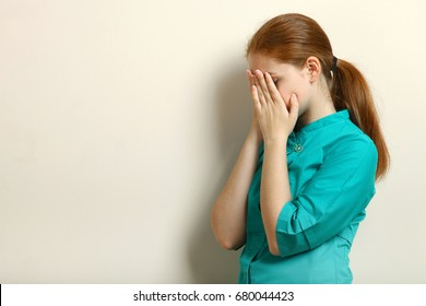 Young nurse is crying on a neutral background
