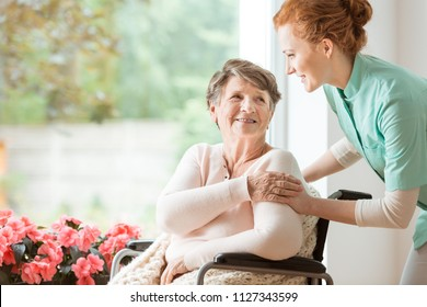 Young nurse helping an elderly woman in a wheelchair. Nursing home concept