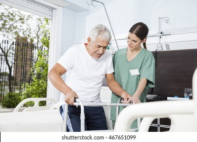 Young Nurse Helping Patient In Using Walker At Nursing Home