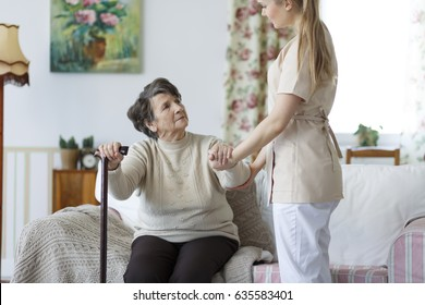 Young nurse helping sad elderly woman to stand up from the sofa