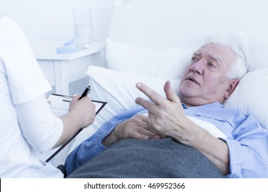 Young nurse making anamnesis with the senior patient lying on a hospital bed
