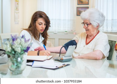 Young nurse measuring blood pressure of elderly woman at home.