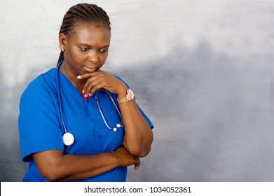 a young nurse standing with a stethoscope on her neck under her chin, thinking.