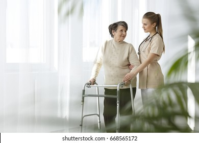 Young nurse taking care of her senior lady patient