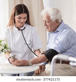 Young nurse is taking elder man's blood