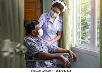Young nurse wearing medical protective mask taking care of an elderly patient sitting in a wheelchair in hospital room.