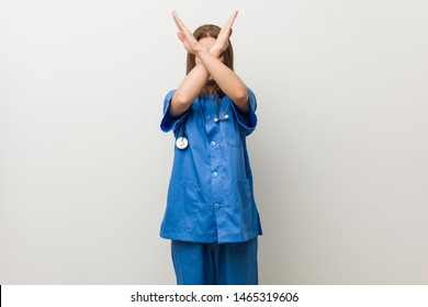 Young nurse woman against a white wall keeping two arms crossed, denial concept.