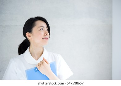 Young nurse woman holding file against concrete wall