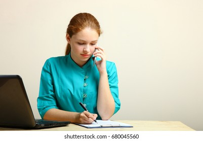 Young nurse working on laptop on neutral background