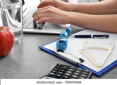Young nutritionist working with laptop in clinic. Weight loss concept